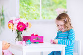 Little girl sewing a dress for her doll — Stock Photo