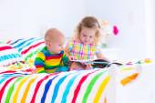 Children reading a book in bed — Stock Photo