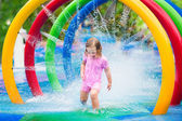 Little girl playing with fountain — Stock Photo