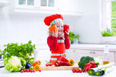 Little girl making salad for dinner — Stock Photo