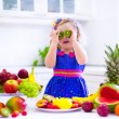 Cute curly little girl in a colorful summer dress eating fresh tropical fruit and berry for healthy breakfast snack in a white sunny family kitchen — Stock Photo #67092367