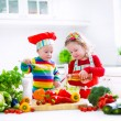 Kids cooking vegetables in a white kitchen — Stock Photo #67093321