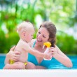 Mother applying sun screen on baby in swimming pool — Stock Photo #67093489