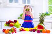 Cute curly little girl in a colorful summer dress eating fresh tropical fruit and berry for healthy breakfast snack in a white sunny family kitchen — Stock Photo