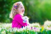 Little girl playing with a rabbit — Stock Photo
