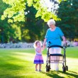 Постер, плакат: Senior lady with a walker and little girl in a park