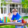 Child reading and eating sandwich at school yard — Stock Photo #69958075