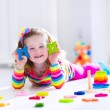 Little girl playing with wooden toys — Stock Photo #69958107