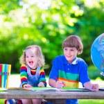 Children doing homework in school yard — Stock Photo #69958169