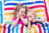 Children sleeping under colorful blanket — Stock Photo