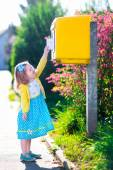 Little girl with an envelope next to a mail box — Stockfoto