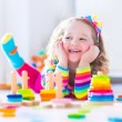 Little girl playing with wooden toys — Stock Photo #72476425