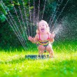 Little girl playing with garden water sprinkler — Stock Photo #73391109