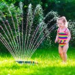 Little girl playing with garden water sprinkler — Stock Photo #73391115