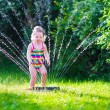 Little girl playing with garden water sprinkler — Stock Photo #73391309