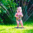 Little girl playing with garden water sprinkler — Stock Photo #73391313