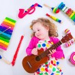 Little girl with music instruments — Stock Photo #73391397