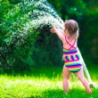 Little girl playing with garden water sprinkler — Stock Photo #73391447