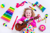Little girl with music instruments — Stock Photo