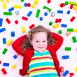 Little girl playing with wooden blocks — Stock Photo #73951347