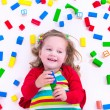 Little girl playing with wooden blocks — Stock Photo #73951373