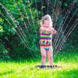 Little girl playing with garden water sprinkler — Stock Photo #74164985