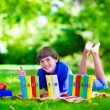 Student boy relaxing in school yard reading books — Stock Photo #74647743