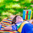 Student boy relaxing in school yard reading books — Stock Photo #74647751