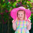 Little girl in a hat in blooming summer garden — Stock Photo #74647757