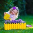 Little girl working in the garden watering flowers — Stock Photo #74647769
