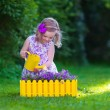 Little girl working in the garden watering flowers — Stock Photo #74647867