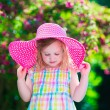 Little girl in a hat in blooming summer garden — Stock Photo #74647913