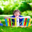 Student boy relaxing in school yard reading books — Stock Photo #74647931