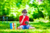 Child in school yard with magnifying glass — Stock Photo