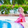 Little girl drinking juice at a swimming pool — Stock Photo #75066515