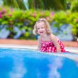 Little girl drinking juice at a swimming pool — Stock Photo #75066567