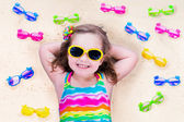 Little girl with sun glasses on a beach — Stock Photo