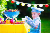Little boy at garden grill party — Stock Photo