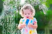 маленькая девочка, мытье окон — Стоковое фото