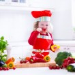 Little girl in chef hat preparing lunch — Stock Photo #76714481