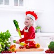 Little girl in chef hat preparing lunch — Stock Photo #76714549