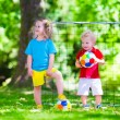 Children playing football outdoors — Stock Photo #76922049