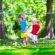 Children playing football outdoors — Stock Photo #77487104