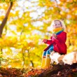 Little girl playing in autumn park — Stock Photo #78963862
