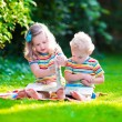Two kids reading in summer garden — ストック写真 #78964188
