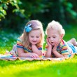 Two kids reading in summer garden — ストック写真 #78964346