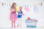 Kids ironing clothes for baby brother — Stock Photo