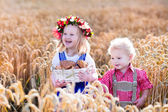 Kids in Bavarian costumes in wheat field — Stock Photo
