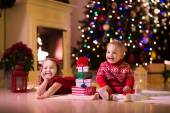 Kids opening Christmas presents at fireplace — Stock Photo