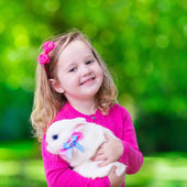 Little girl playing with rabbit — Stock Photo